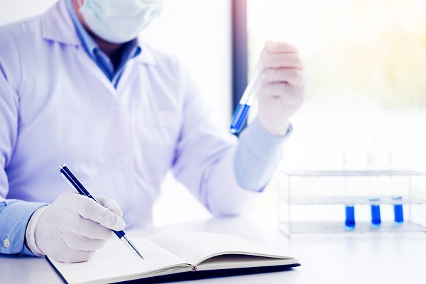 Scientist in white coat holding and examining test tube with reagent making notes of his research in laboratory.